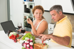 Serious woman looking at her husband preparing vegetables salad. Mature man cutting cucumbers and tomatoes in the kitchen.