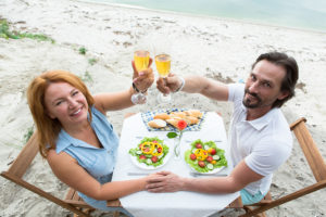 Mature couple demonstrating glasses of white wine in the restaurant while having date. Man and woman smiling for photographer.